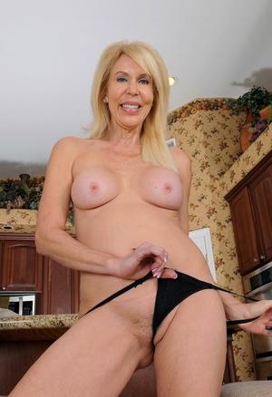Big titted mature housewife Erica Lauren finger spreads her bush in kitchen