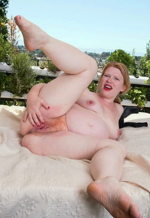 Pregnant redhead Madison Young finger opens up her hairy twat in the naked