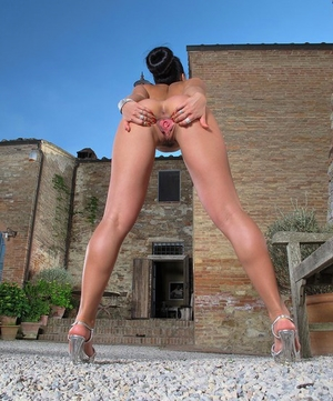 Naughty brunette Taissia Shanti frees cunt from crotchless panties outdoors
