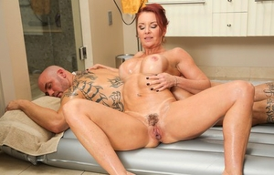 Big-chested redhead Janet Mason rides a client's cock during a utter service rubdown