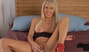 Sexy older woman Erica Lauren toys her pussy in red heels